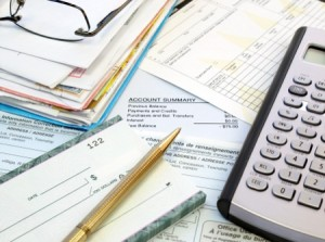 Pile of statements, checkbook and calculator, image from Shutterstock